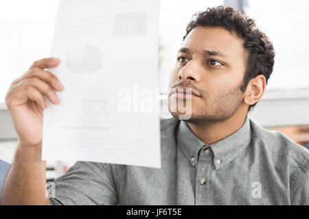 Close-up portrait of young concentrated businessman holding paper indoors - Stock Photo