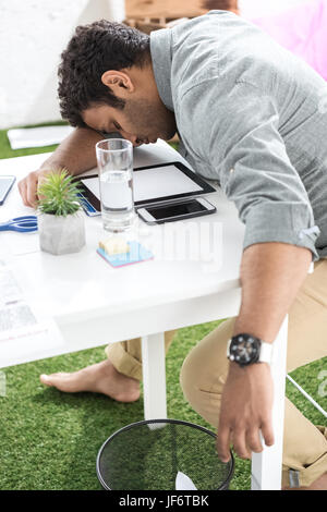Young african american businessman sleeping on the table at modern office - Stock Photo