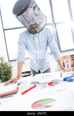 portrait of businessman with trash bucket on head in office, business establishment - Stock Photo