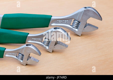 Three adjustable wrenches in row on wood - Stock Photo