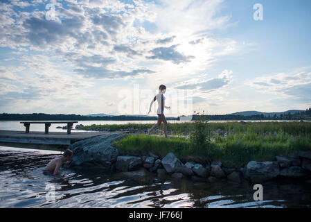 Boy and girl swimming in lake - Stock Photo