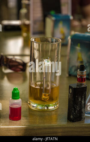 Vaporizer and almost empty beer with bottle and fork on table - Stock Photo