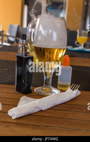 Vaporizer and smoking beer with bottle and fork on table - Stock Photo