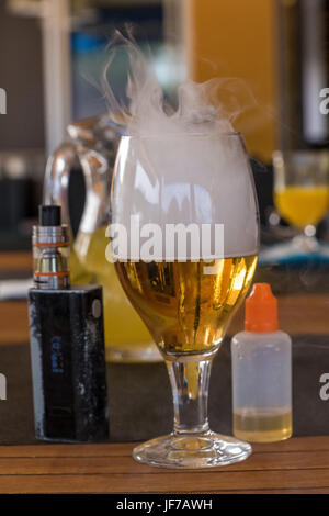 Vaporizer and smoking beer with bottle on table - Stock Photo