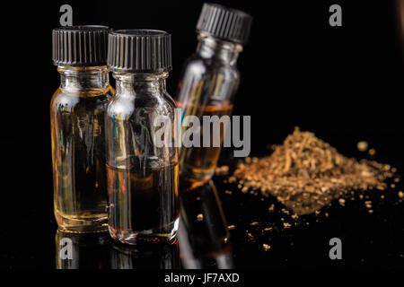 E-liquid bottles next to grinded tobacco leaves - Stock Photo