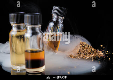 E-liquid bottles next to grinded tobacco leaves and smoke cloud - Stock Photo