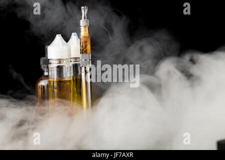 Electronic cigarette with bottles and big cloud of smoke - Stock Photo