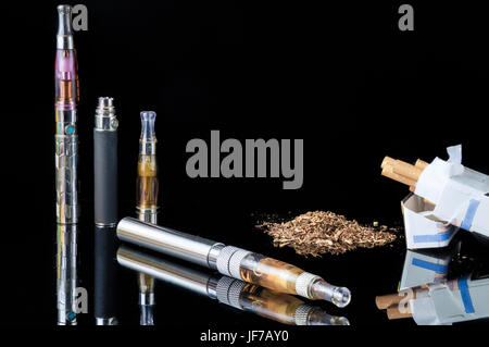 E-cigarette with pile of grinded tobacco leaves and a pack of smokes [FIX] - Stock Photo