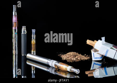 E-cigarette with pile of grinded tobacco leaves and a pack of smokes - Stock Photo