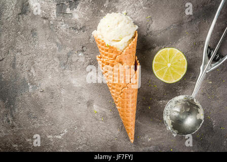 Homemade lemon ice cream. Horn with sorbet, sprinkled with zest, spoon and half lime. On a gray concrete old table. - Stock Photo