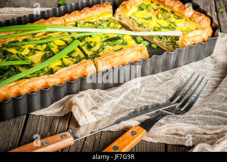 French home cooking. Casserole. Pie. quiche lorraine from puff pastry, with young green onions and spinach. On old - Stock Photo