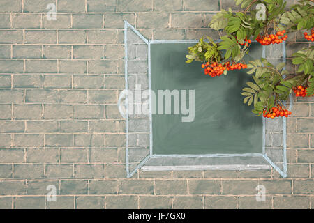 Branches of rowan tree before illustration on a chalkboard of the open window - Stock Photo