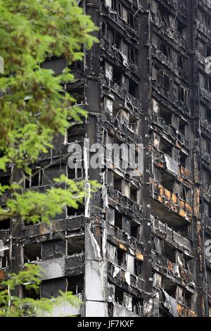 Grenfell Tower burnt out shell and tributes to the dead - Stock Photo