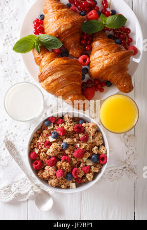 Muesli with berries and croissants, milk and orange juice close-up on the table. vertical view from above - Stock Photo