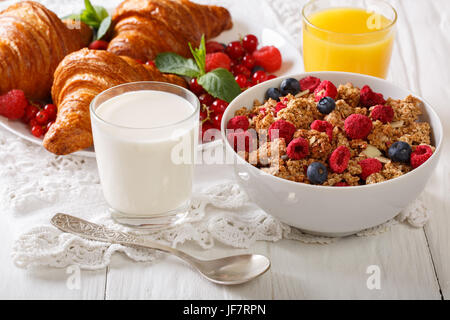 Homemade granola with berries, croissants, milk and juice closeup on the table. horizontal - Stock Photo