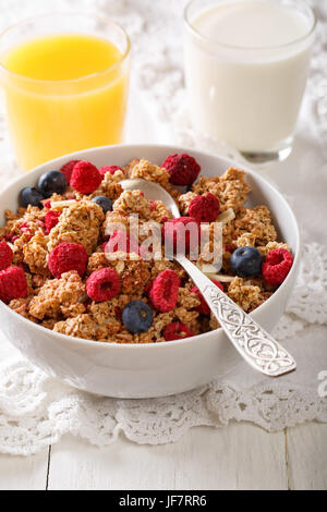 Baked granola with dried raspberries and blueberries, milk and juice close-up on a table. vertical - Stock Photo