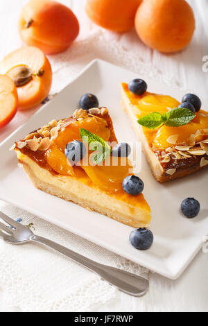 Apricot pie with blueberries and nuts close-up on a plate. vertical - Stock Photo