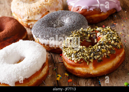 Homemade glazed multicolored donuts close-up on the table. horizontal - Stock Photo