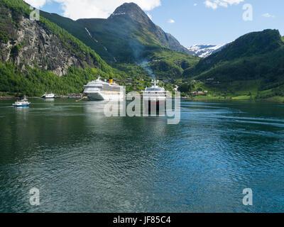 Looking along Geirangerfjorden Geiranger village with moored cruise ship and departing Hurtigruten post boat Sunnmøre - Stock Photo