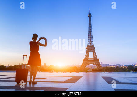 Woman traveler taking a photo of Eiffel Tower from Trocadero with her smartphone during a weekend trip to Paris, - Stock Photo