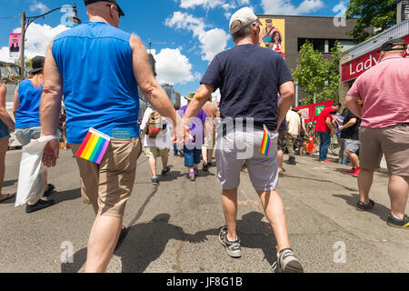 Toronto, CA - 24 June 2017: Gay couple holding hands and walking on Church Street in the Gay Village. - Stock Photo
