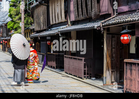 Japanese couple dressed in traditional costume, having their photographs taken a few days before the actual wedding. - Stock Photo