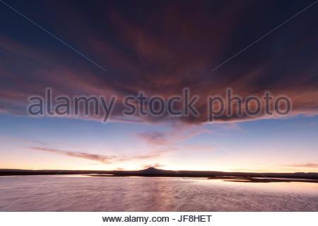 Red clouds at sunset over Chaxa lagoon in the Salar de Atacama. - Stock Photo