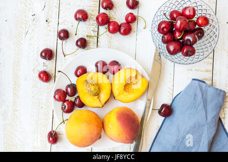 Ripe colorful peaches halved and whole, sweet cherries on white plate, crystal bowl, knife, plank wood table, blue napkin, styled arrangement, flat la