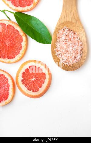 Ayurveda face skin scrub ingredients, pink Himalayan salt in wooden spoon, sliced grapefruit, green leaf on white - Stock Photo