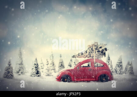 Retro toy car carrying tiny Christmas tree. Fairytale, miniature scenery with snow and forest. - Stock Photo
