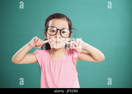 Happy little Asian girl with glasses smiling isolated on vintage mint green background . - Stock Photo