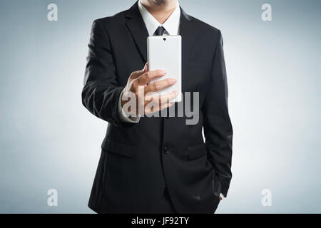 Smart businessman in black suit standing while make a selfie by hand phone on grey background . - Stock Photo