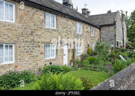 Row of cottages including Plague Cottage where inhabitants died due to the plague in Eyam in the Derbyshire Peak - Stock Photo