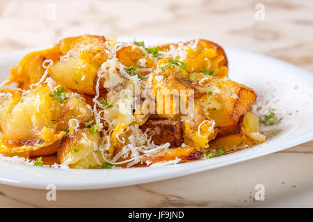 Fried potatoes with scrambled eggs and parmesan cheese on white plate - Stock Photo