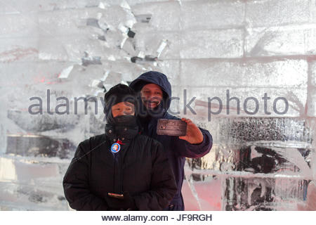 A married couple take a photo of themselves at a model of the ice hotel in Quebec City during Winter Carnival. - Stock Photo