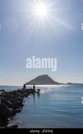 Mount Maunganui on horizon under blue sunny sky and small unrecognizable fishermen in distance - Stock Photo