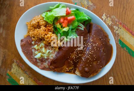 Enchiladas mole, with refried beans, brown rice and salad - Stock Photo