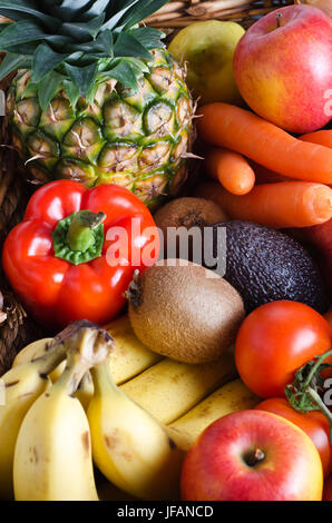 Overhead shot of a selection of fresh fruit and vegetables in a wicker basket.  Portrait orientation. - Stock Photo