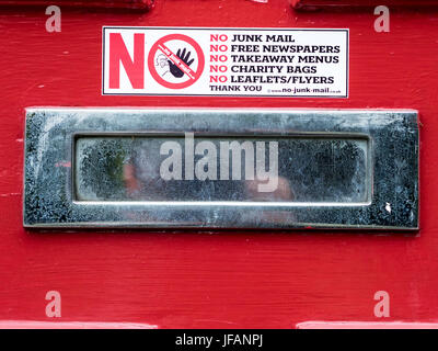 Notice on a letter box requesting NO Junk Mail, free newspapers, takeaway menus, charity bags, leaflets & flyers - Stock Photo