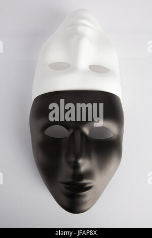 Black and white masks joined on white reflective background. Vertical image, top view. Anonymity concept. - Stock Photo