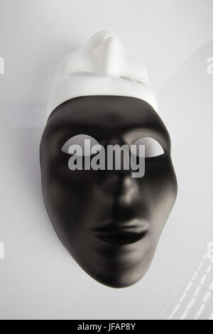 Black and white masks joined on white reflective background. Wide angle, vertical image, top view. - Stock Photo
