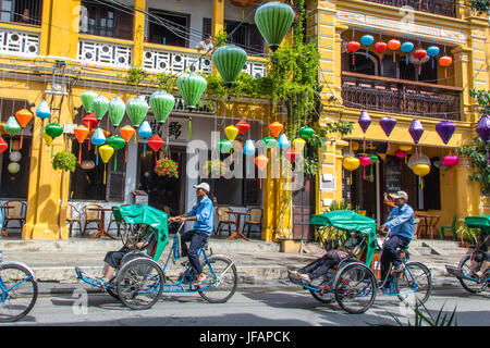 Tourists on a cyclo tour, colorful lanterns in Hoi An, Vietnam - Stock Photo