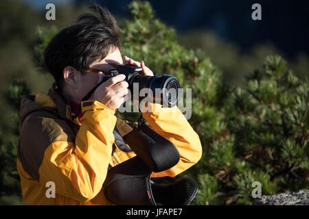 Chinese photographer with an SLR Camera, Huangshan Mountains, China - Stock Photo