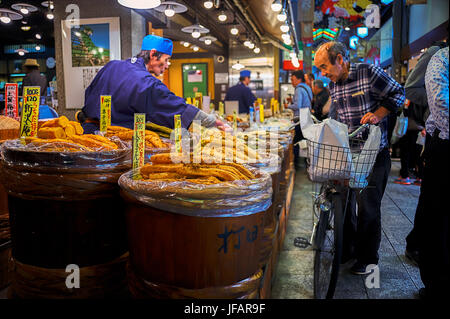 Nishiki Market, Kyoto, – October 22, 2016: Old man came with his bicycle stood in front of a store asking the vendor - Stock Photo