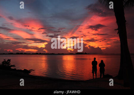 Silhouetted couple by palm tree watching a spectacular red, yellow and purple sunset exploding behind dark clouds, - Stock Photo