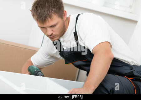 Man putting together self assembly furniture in new home. DIY, new home and moving concept - Stock Photo