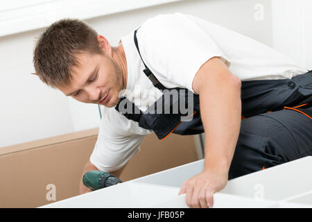 Smiling man putting together self assembly furniture in new home. DIY, new home and moving concept - Stock Photo