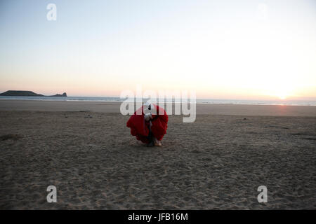 A Paraglider has landed on a beach at sunset, - Stock Photo