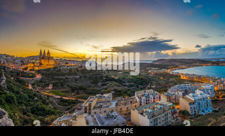 Il-Mellieha, Malta - Beautiful panoramic skyline view of Mellieha town at sunset with Paris Church and Mellieha - Stock Photo