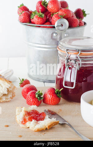 A farmhouse kitchen table scene of freshly made strawberry jam in storage jar with a tin pail of strawberries in - Stock Photo